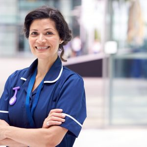 Portrait Of Mature Female Nurse Wearing Uniform Standing In Modern Hospital Building